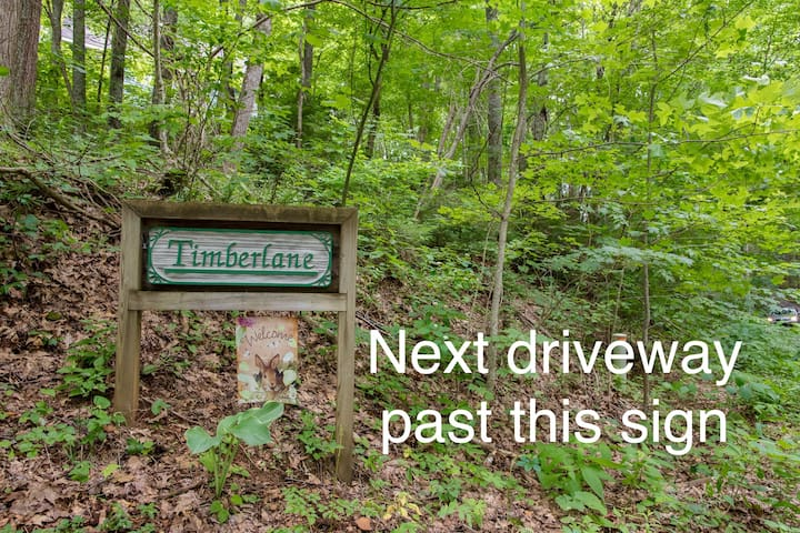 """Ours is the green house sitting above this Timberlane sign with """"welcome"""" flag."""