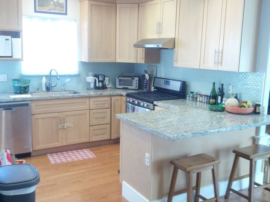 Kitchen features toaster oven, microwave, dishwasher, coffee machine, and counter seating.