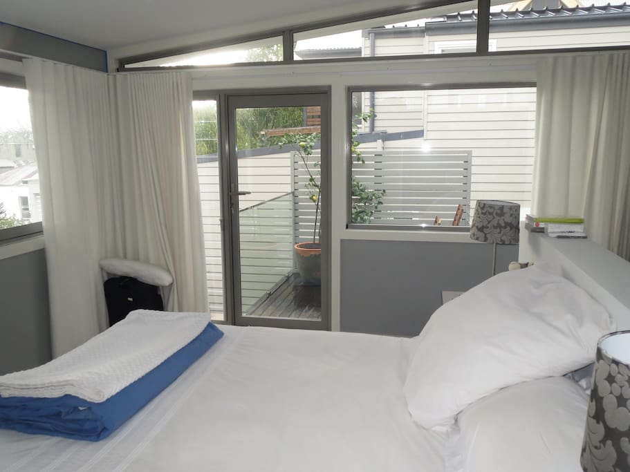 A spacious ensuite bedroom with an adjoining deck