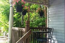 The porch has an outdoor table, chairs and bench, and a view of historic houses and downtown Ithaca.