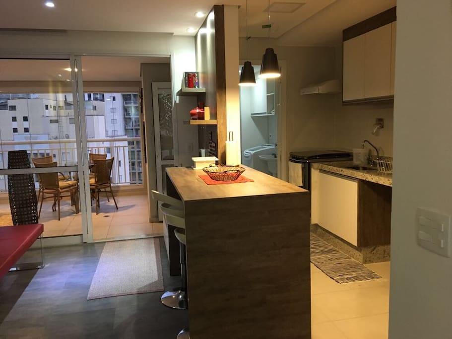 Vista lateral da cozinha estilo americana e varanda com mesa e churrasqueira.