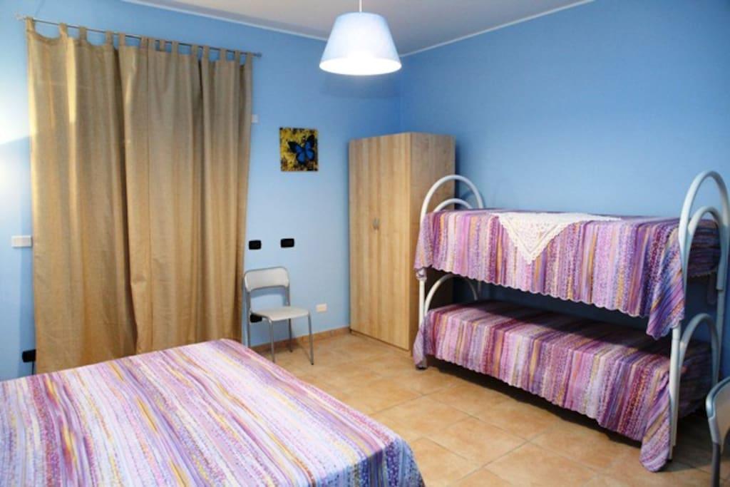 Camera Azzurra per 4 ospiti con porta/finestra sul terrazzo esterno.
