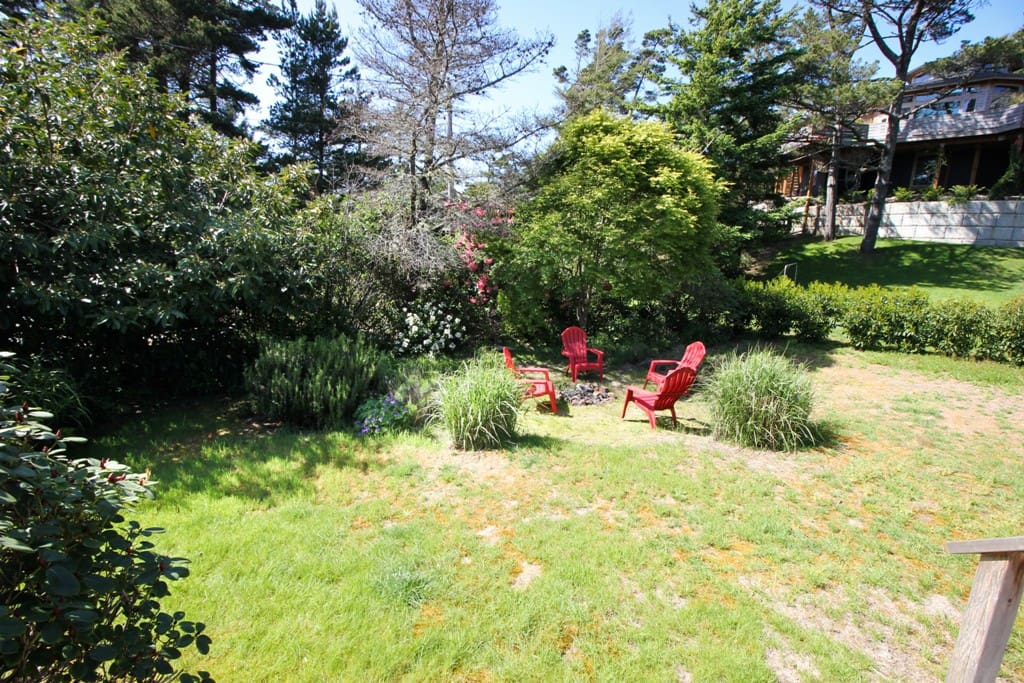 Large grassy landscaped backyard with fire pit and deck with table, chairs and charcoal BBQ.