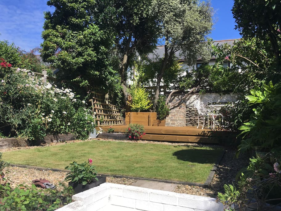 Very sheltered, sunny garden with steps up to a small lawn and wooden deck. Dine outside on the raised deck furnished with a gas BBQ, round metal table and four chairs. A small shed by the kitchen door has a rotary airer and a folding sun lounger.