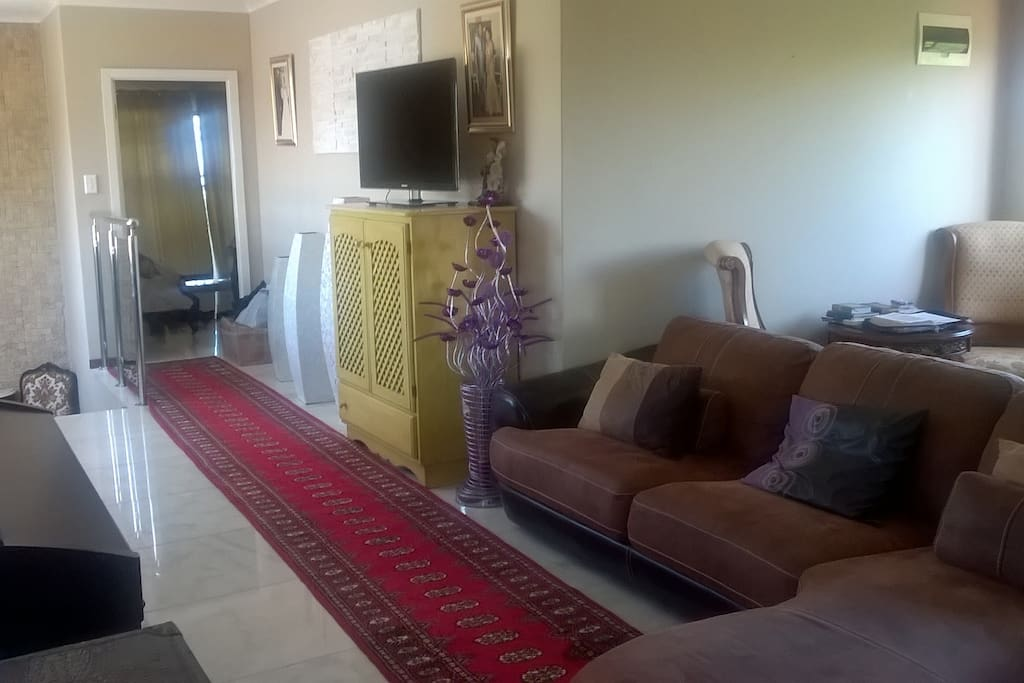 lounge area with large sofa that can be used as a bed. Piano. Also large dining table.