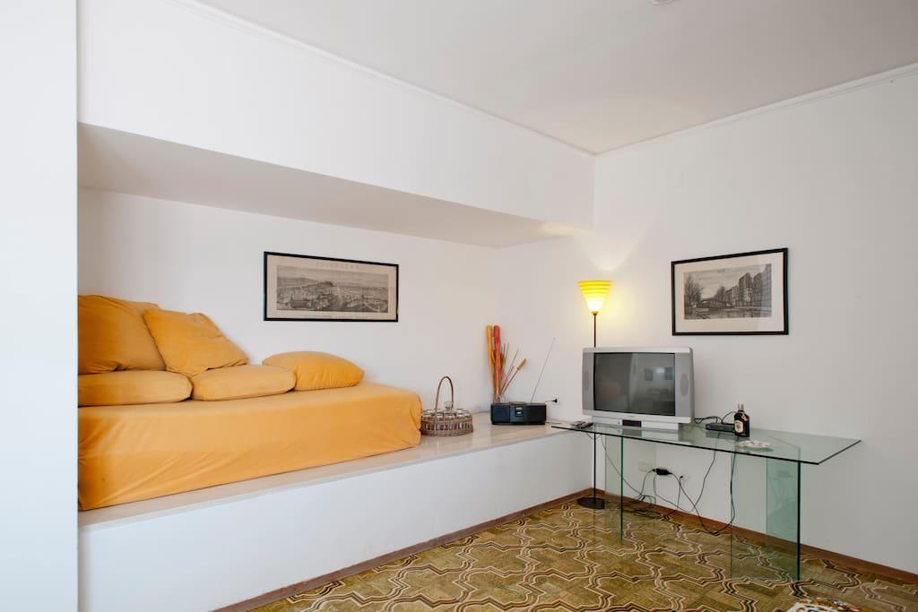 Il salotto con televisore, due letti e un divano letto