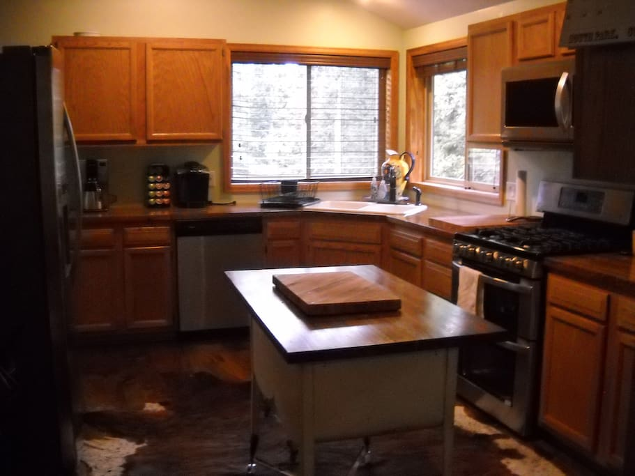 Large kitchen, fully equipped with eat in bar, butcher block counter tops and new gas range, fridge and microwave