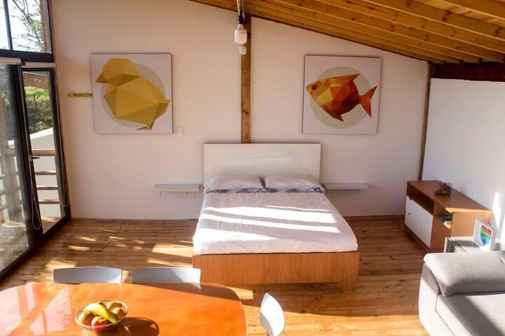 El interior del apartamento es tipo loft, donde se encuentra una cama doble, un sofa cama y la mesa del comedor.
