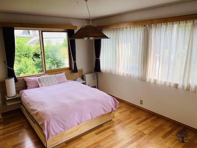 2階マスターベッドルームは、クィーンベッド1台。大きな窓から太陽の光も十分に入ります。緑の樹々が生い茂ります。お部屋内に大きなクローゼットも完備。