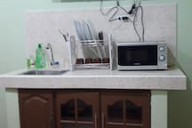This is the dishwashing area with liquid hand soap, dishwashing liquid,  dishes & silverwares,  microwave oven for easy heating of ready to eat foods and cabinet below.  Above is the TV connected to ABS-CBN plus.  The TV has a Netflix subscription.