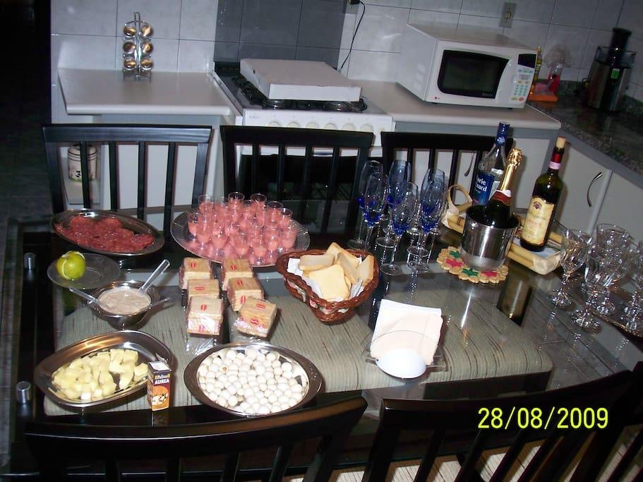 Cozinha com geladeira, fogão, micro-ondas, armários e mesa