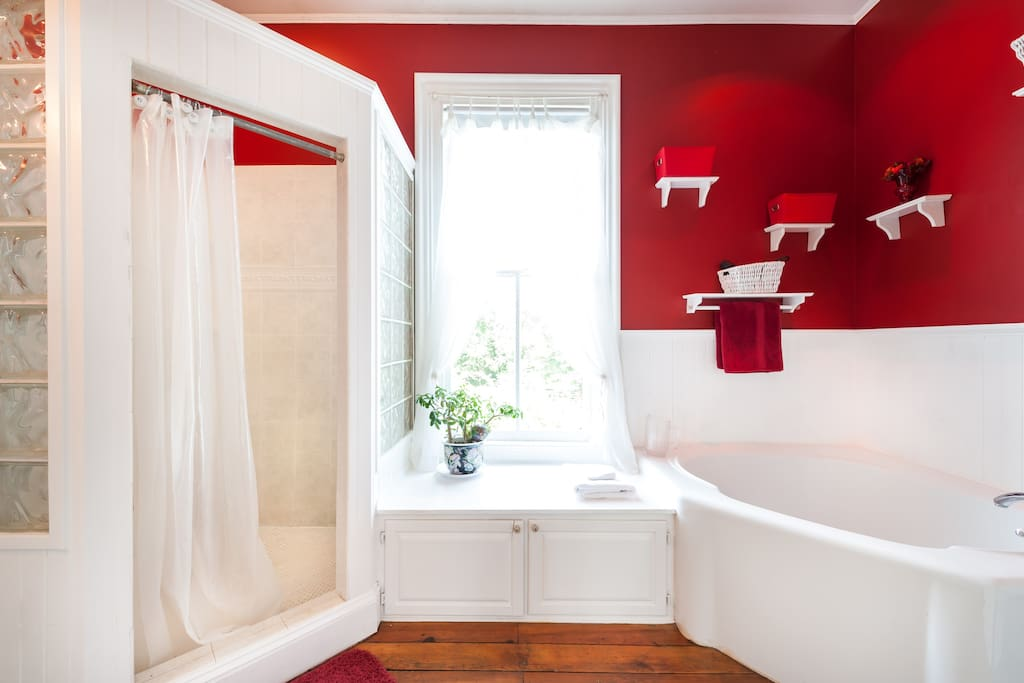 The shared luxury bath with triangular soaking tub and glass block shower