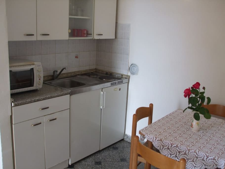 the kitchen has a dining table, cooker and spacious fridge