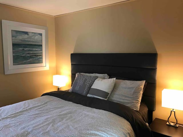 Comfy queen bed with bedside tables and lamps.