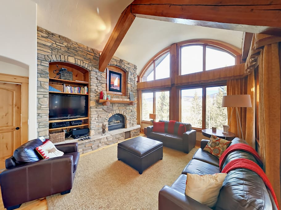 The grand living room boasts vaulted ceilings, exposed log beams, floor-to-ceiling windows, and a stone wall with a gas fireplace.