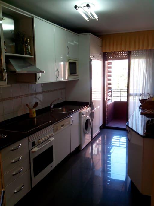 cocina completa, con microondas, nevera, lavadora, horno y vitro, mesa de cocina con 4 sillas y pequeña terraza.