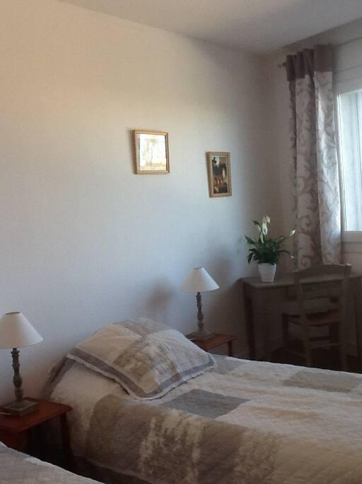 une chambre à deux lits individuels aux tons clairs et pastels
