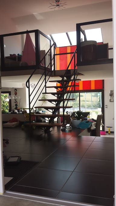 Entrée avec vue sur la mezzanine, la salle à manger, la cuisine, le salon et l'arrière de la maison