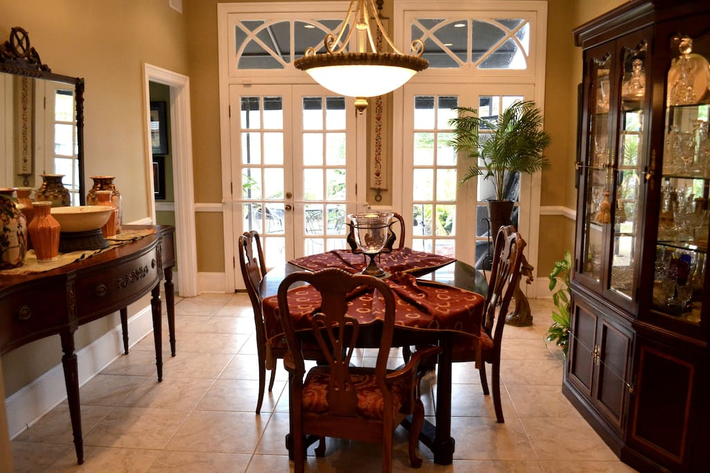The spacious formal dining room looks out through imported antique French doors from New Orleans onto a professionally landscaped courtyard. The courtyard has a casual dining table and chairs on an awning covered patio. Enjoy privacy with the 6 ft. brick