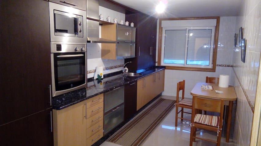 Amplia cocina con electrodomésticos, lavadora y lavavajillas