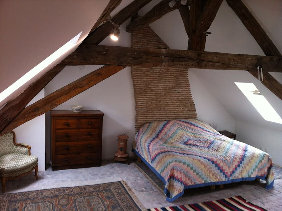 brand new kingsize double bed against original and restored natural brick chimney