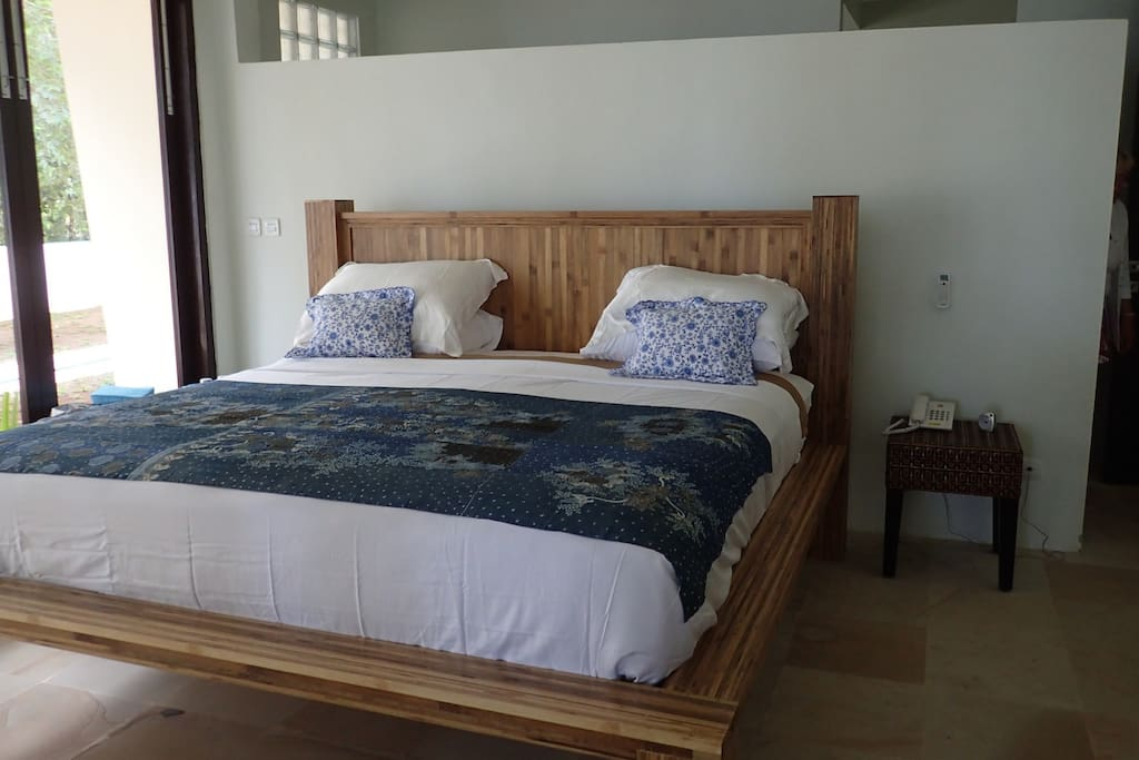 A Bedroom  - with bamboo bed, en-suite dressing area and bathroom behind bed