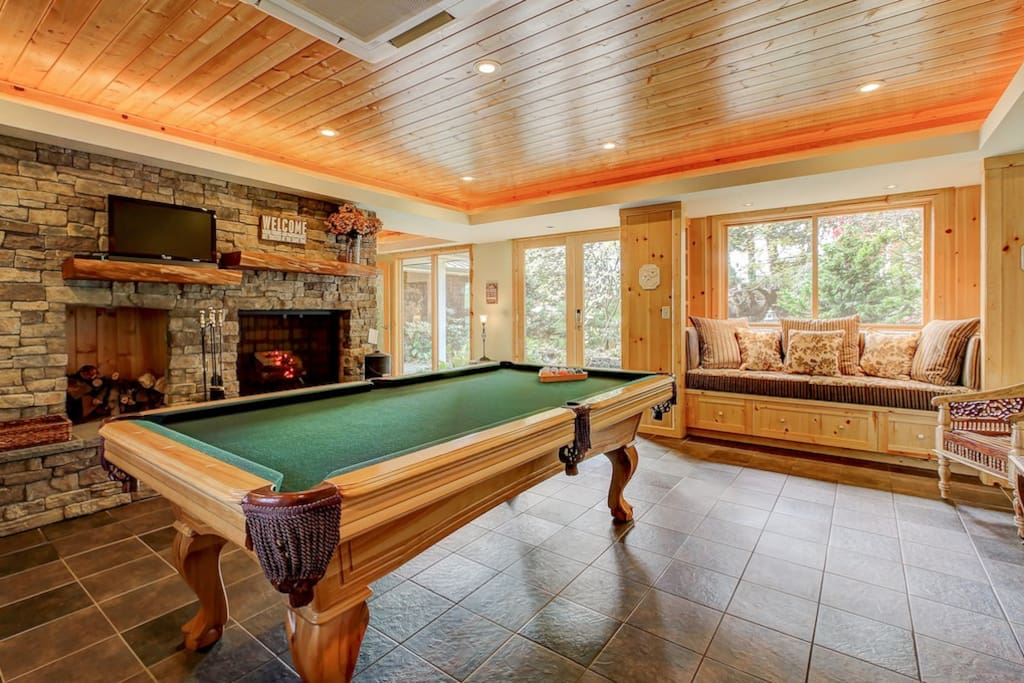 "Fun billiard/game room with real fireplace greets you upon arrival through an additional front entrance door! Room also features cozy window seat that overlooks a beautifully landscaped ""island"" nestled in a circular walk up...wonderful for reading a book. There is also a desk and printer if work just won't let you get away! This room can be closed off from the rest of house via double french doors (just in case you might have little ones sleeping)."