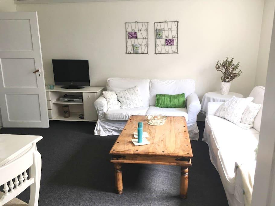 Stue. 3 + 2 personers sofaer, lille spisebord og TV.