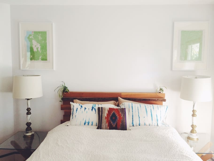 Your upstairs bedroom with local vintage maps on the wall and a bed frame made by a local artist.