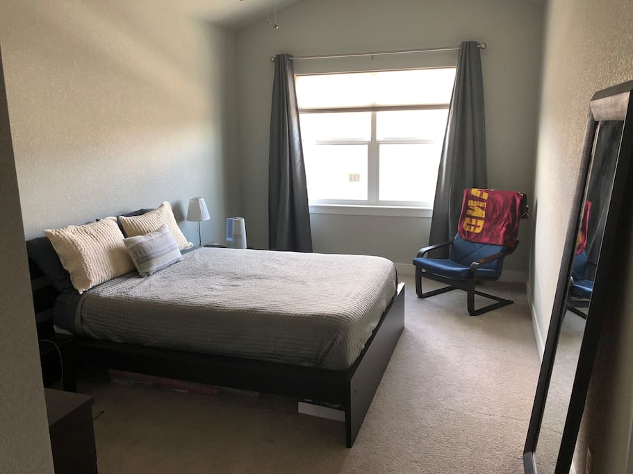 Master bedroom has a queen bed and plenty of space including a chair to relax and read in