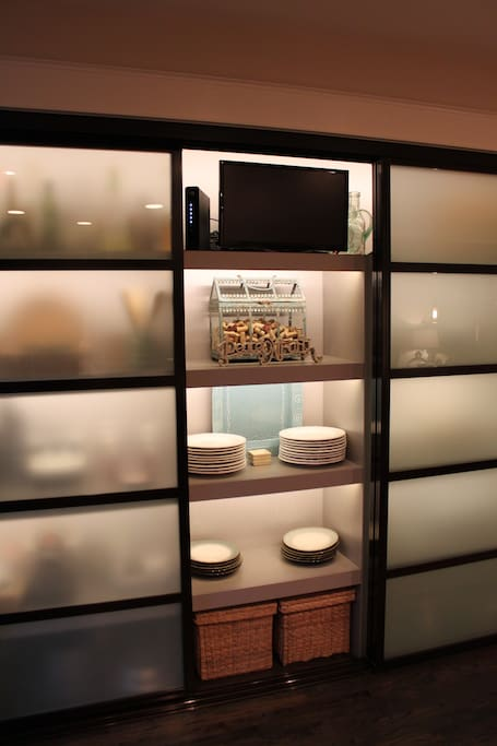 Beautiful custom pantry glass doors with easy glides  and built in TV