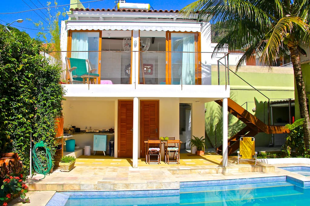 Front view of guest house on bright day. Guest house has two small cute suites sharing a balcony, overlooking salt-water swimming pool. Independent kitchen area below.