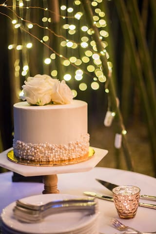 The wedding cake with a backdrop of fairy lights and the bamboo forest