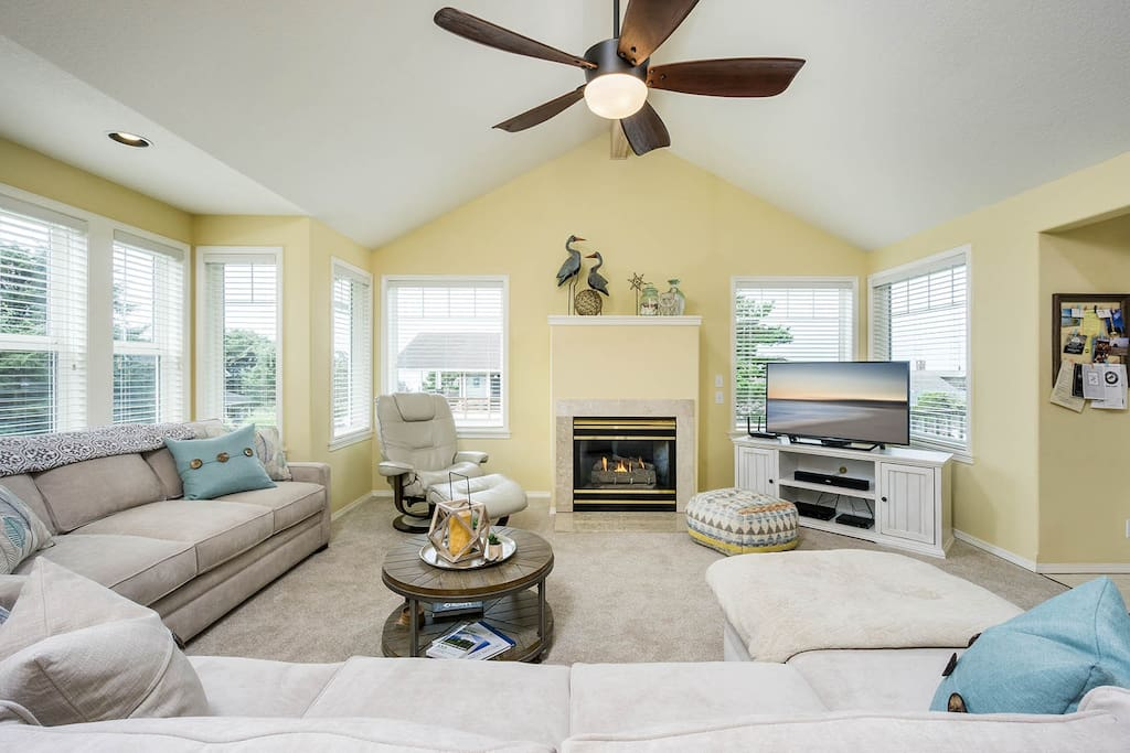 Light-filled living room with gas fireplace and comfy sectional couch (folds out to queen sleeper for extra accommodations).