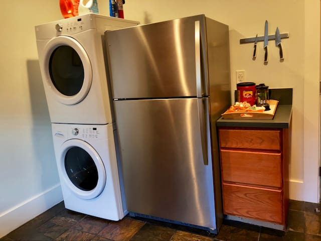Brand new washer/dryer in kitchen with detergent for guest use.