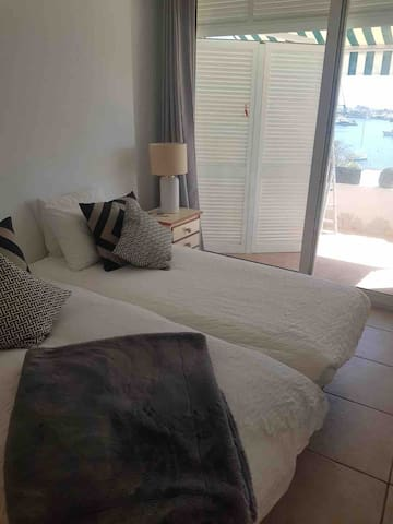 Master bedroom. Stunning view of beach and Port Adriano. Two singles. Portable air conditioning & large ceiling fan  Memory foam topper, comfortable beds are so important! Zoom to see the amazing view.