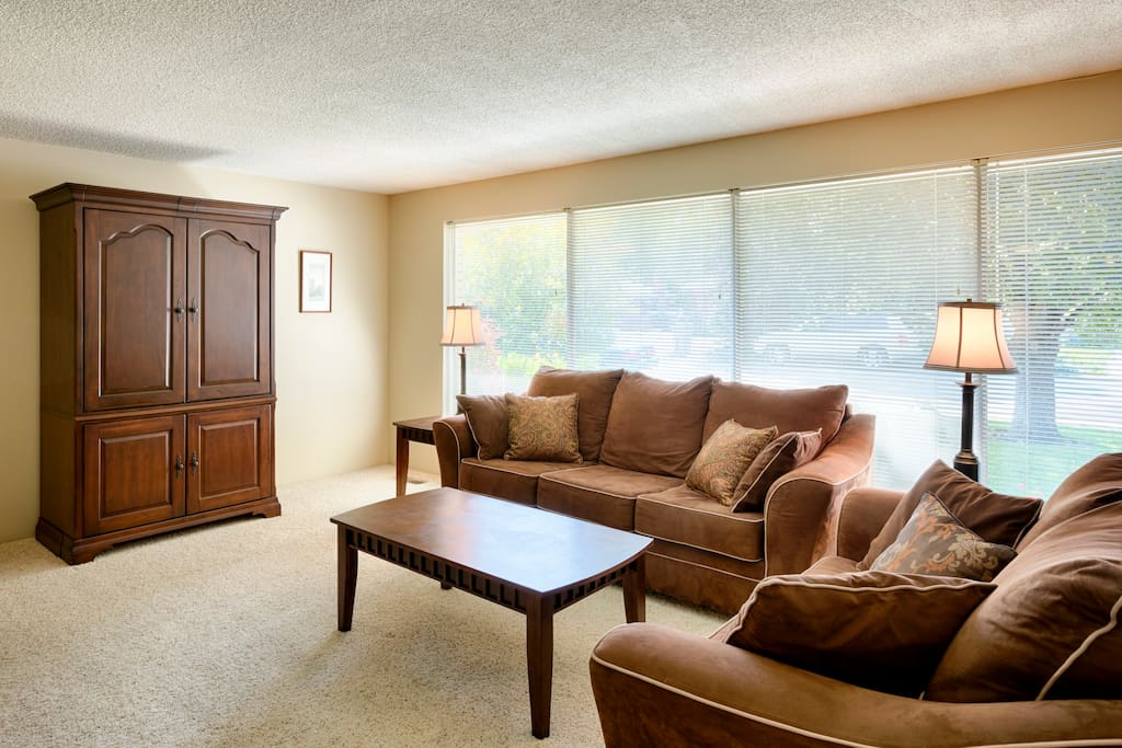 Large bank of windows in living room with flat-screen TV