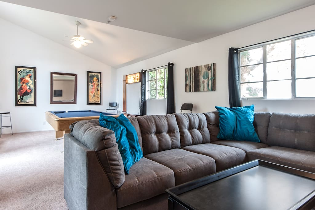 Oversized, comfortable sectional couch and 2 additional club chairs. 4 additional tall chairs around pool table