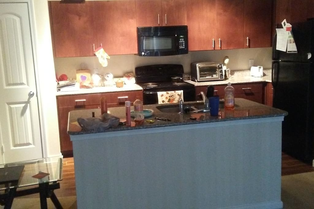 Open concept kitchen with mid size island. Cleaning after a great guest stay!