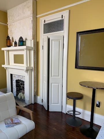 Inside the suite, with a view of the door to the private bathroom, which features a door frame and transom that is original to the house, but refitted for purpose in this space with vintage privacy glass and addition of French doors.