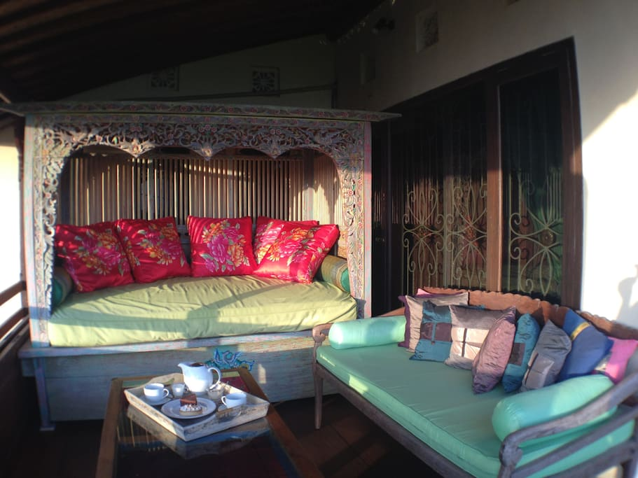 Private balcony featuring an antique carved and hand painted Javanese daybed & Balinese daybed for the enjoyment of sunset drinks or a quiet, comfy spot to relax.