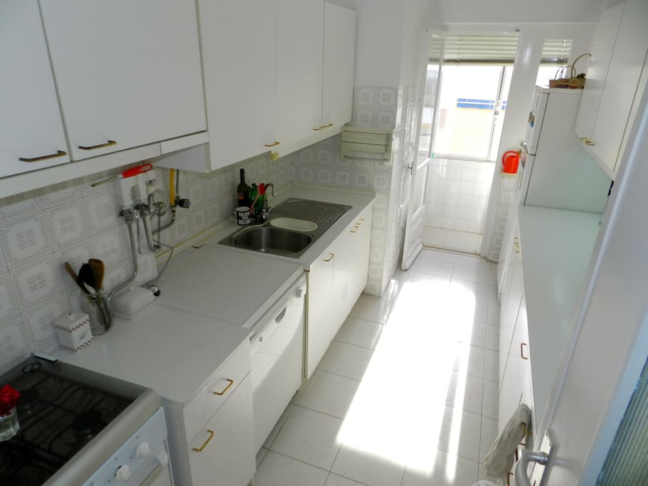 Fully equipped sunny kitchen leading to separate laundry room.