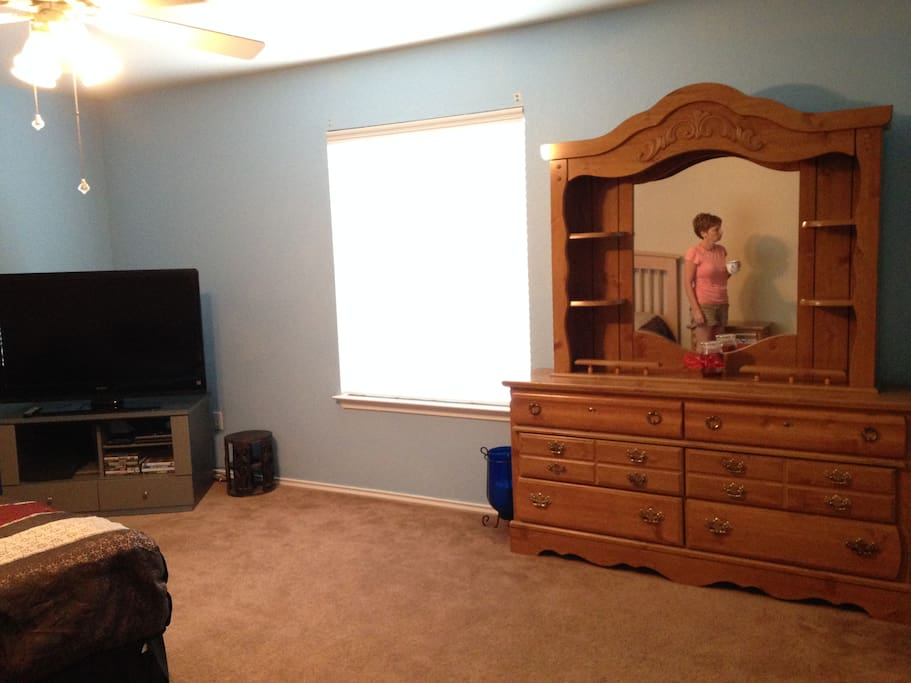 One of our guest rooms. It includes a queen size bed, a flat screen tv with a dvd player, a dresser, and a closet.