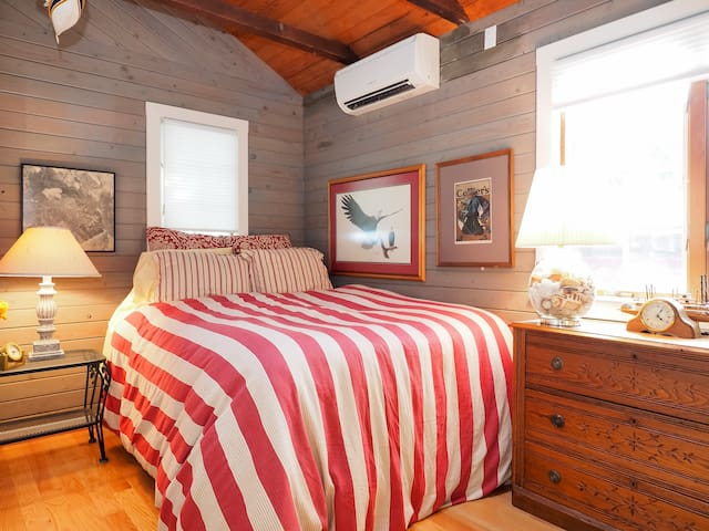 Queen size bed with Pottery Barn linens is in a cozy hideaway between the front porch and dining area.