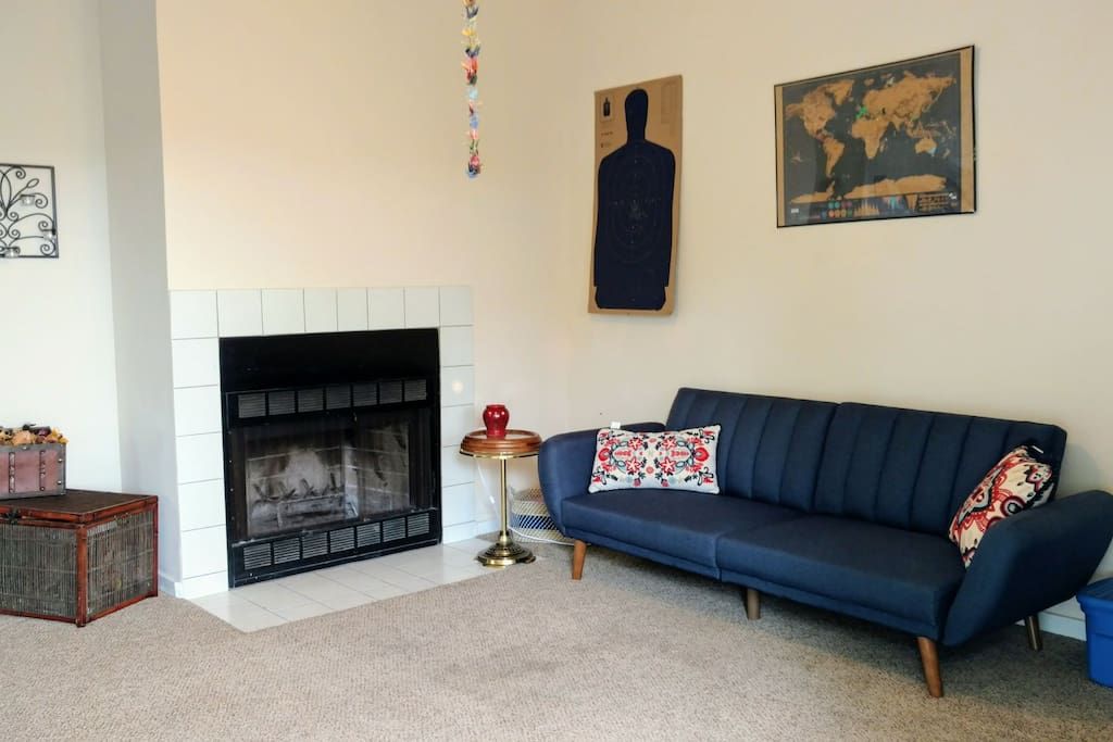 Living room: XL futon and working wood burning fireplace.