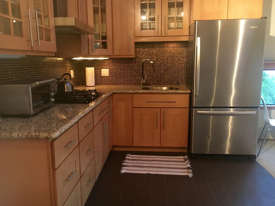 Beautiful new kitchen with 4 burner gas stove, fridge, and toaster oven.