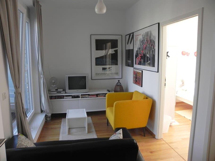 TV corner (now with flatscreen + Netflix) with entrance to rooftop terrace; bathroom door left of sofa