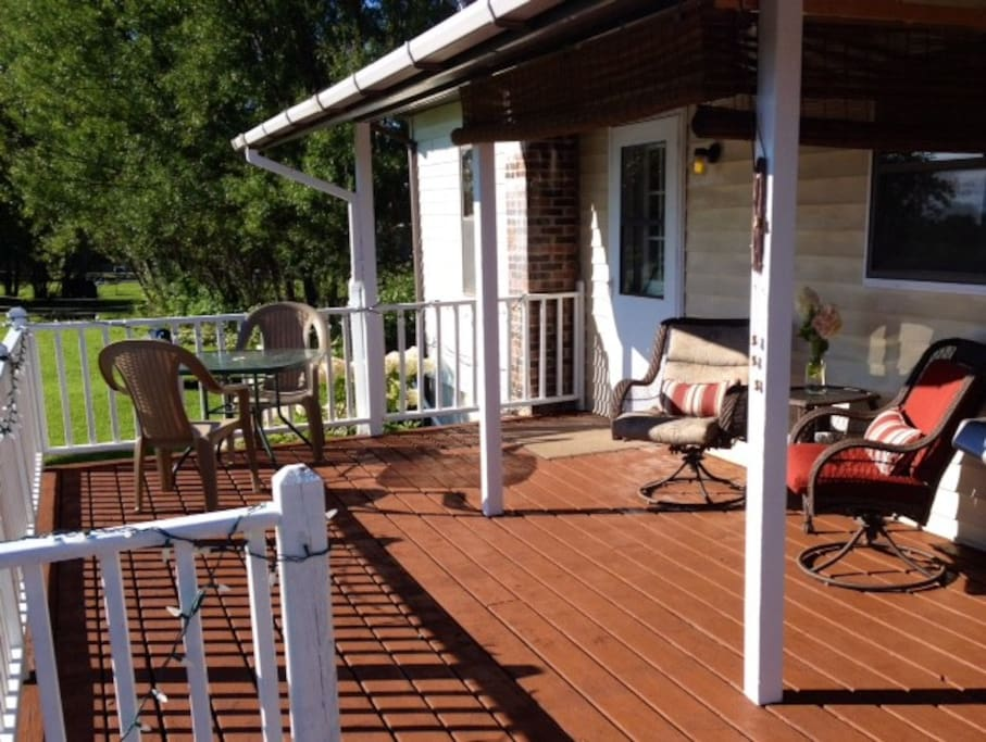 Private deck area has table seating, lounge seating and privacy/light control shades, along with gas grill.
