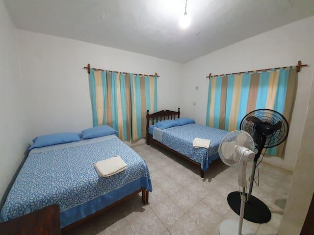 Cuarto 1  Dos camas matrimoniales y sus respectivos ventiladores Le corresponde un baño completo a esta habitación y se encuentra a un lado de la misma