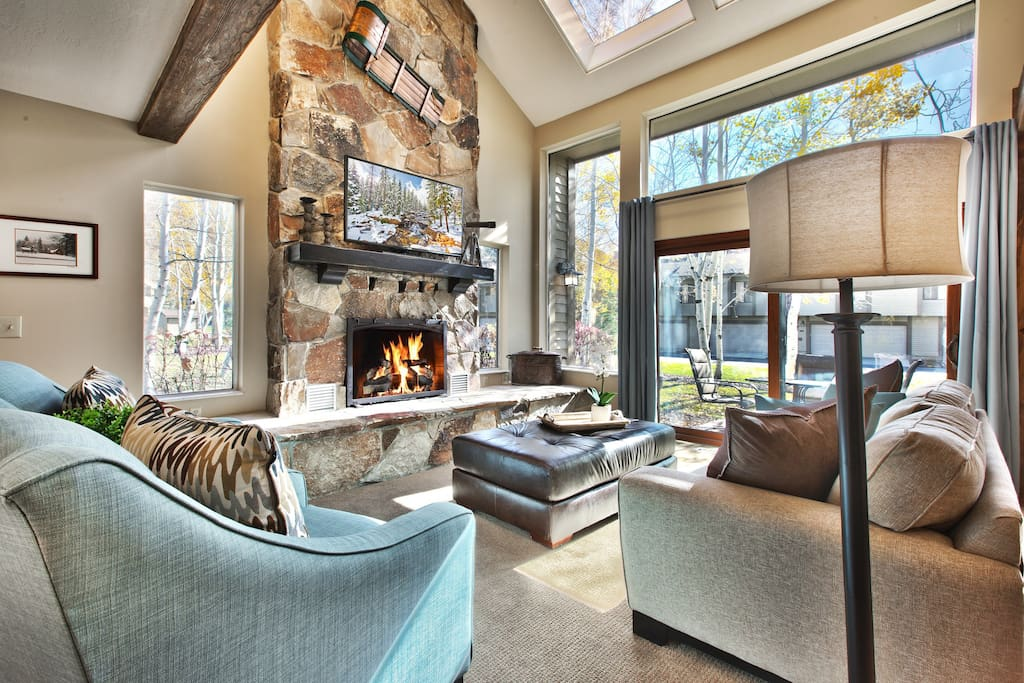 """Living room with soft club chairs and sofa, gas fireplace, and 50"""" HD DVR TV"""